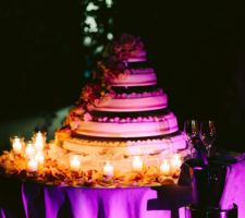 Cutting of the cake with candles and romantic lighting